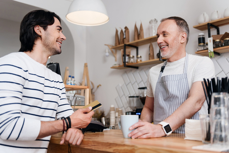 satisfied customer: Satisfied customer. Beautiful young man smiling while giving a credit card to cheerful and content male barista in the cafe who is giving him a cup of coffee t Stock Photo