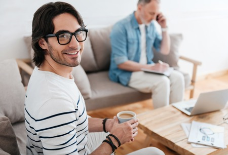 noting: Freelancers team. Smiling young man holding a cup of coffee and looking at a camera with another man sitting, talking per phone and noting something in a background Stock Photo