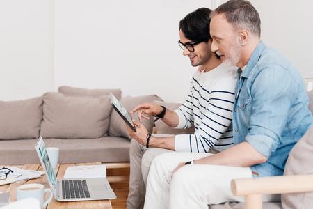 reuniones empresariales: Equipo de negocios. hombres de negocios alegres y de contenido que llevan a cabo y que usa la tableta digital de juntas Foto de archivo