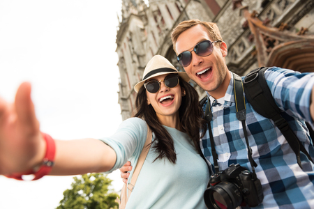 overjoyed: Express yourself. Positive overjoyed tourists smiling and having a walk while traveling together