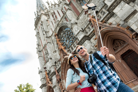 say cheese: Say cheese. Positive smiling delighted couple standing in the street and making selfies while having a walk