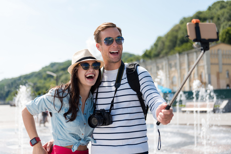 glad: On the edge of joy. Positive smiling overjoyed couple smiling and making selfies near fountain while feeling glad
