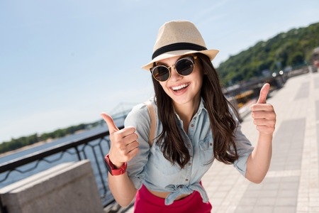Have a great day. Positive beautiful woman smiling and thumbing up while having a walk