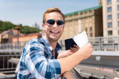 Ready to travel. Cheerful handsome man smiling and holding tickets while leaning on the handrail