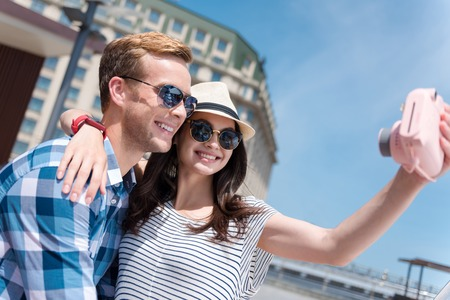 Brightest moments. Cheerful smiling loving couple holding camera and making selfie while having fun