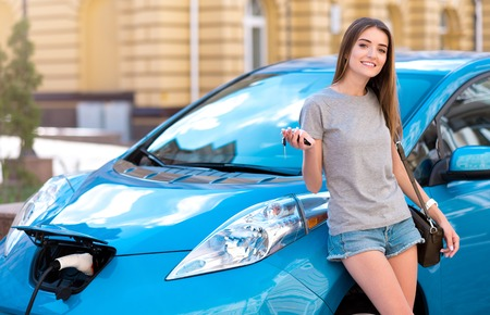 Hey join me. Delighted young woman reclining on her electric car while charging it in the city and holding keys Stock Photo