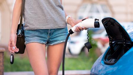 私にとってはとても簡単。もう一方の手でキーを持つ彼女の電気自動車の充電ケーブルを保持している女性のクローズ アップ 写真素材 - 60318879