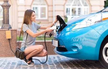 Innovation in my life. Pleasant good looking young woman squatting to charge her eco car in the city