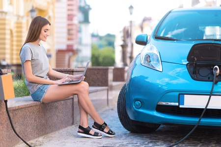 I have some time. Lovely calm woman using a laptop while sitting and charging her hybrid car in the city