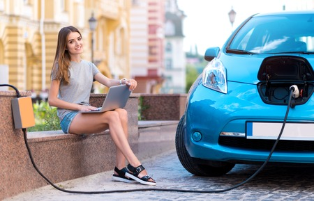 make a choice: Make a choice toward eco. Charming beautiful woman sitting with a laptop on her knees and looking at the camera while charging her electric car Stock Photo