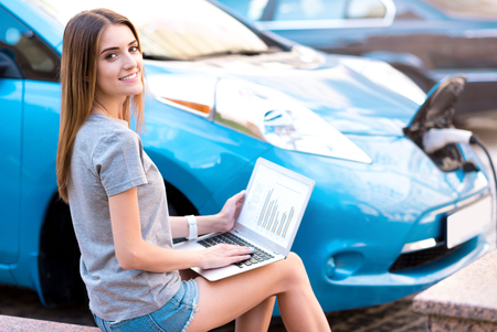 hybrid car: I use time with benefits. Pretty young woman working on her laptop with diagrams on the screen while refueling her hybrid car Stock Photo