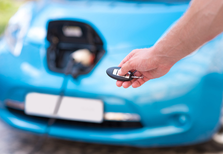 hybrid car: Operate the system easily. Close up of a hand of a man holding key of a hybrid car charging on the background