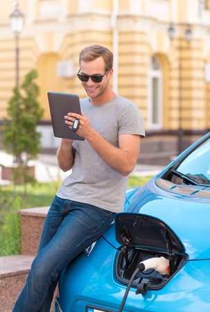Thats so nice. Satisfied young man using a tablet while waiting for charging a battery of his new eco car