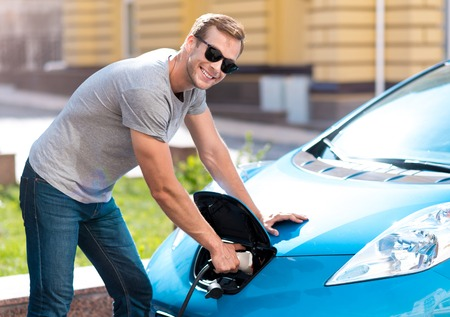 Hey you. Handsome lively young man looking at the camera while holding a power connector in his electric car 写真素材