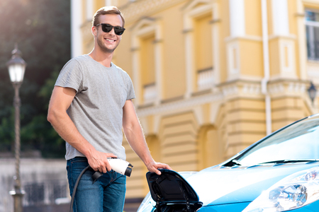 Look how to do it. Smiling contented young man with sunglasses looking at the camera while holding a power cable to his electric car
