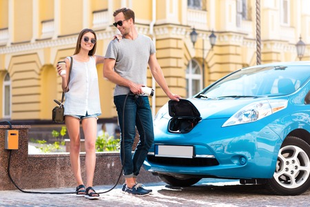 rousing: Our new purchase. Pretty charming young woman with coffee looking at the camera while delighted man holding a power cable to the electric car