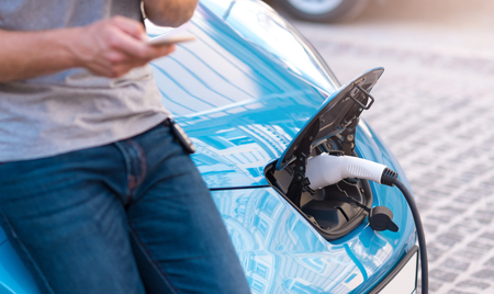 How it is easy and efficient. Close up of a fuel tank of an electric car plugged for refueling with a man holding a smartphone in front of it