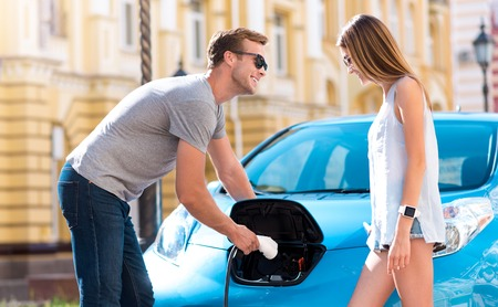 rousing: Look here. Smiling joyful man showing to his girlfriend how to plug a cable for charging a battery on their electric car Stock Photo
