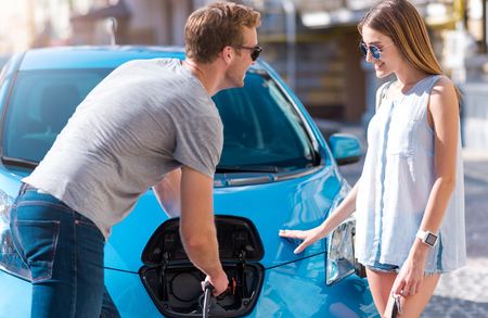 rousing: You are welcome. Smiling pleasant man helping beautiful young woman to charge an electric car Stock Photo