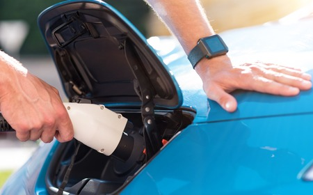 plugged in: New view on cars. Close up of a man charging an electric car with the power cable supply plugged in. Stock Photo