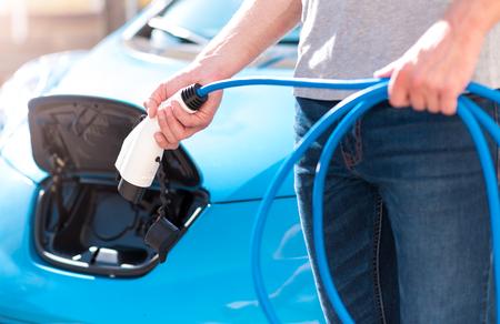 C'est tellement facile à utiliser. Gros plan des mains d'un homme tordant un connecteur d'alimentation pour un véhicule électrique avec une voiture électrique sur le fond Banque d'images