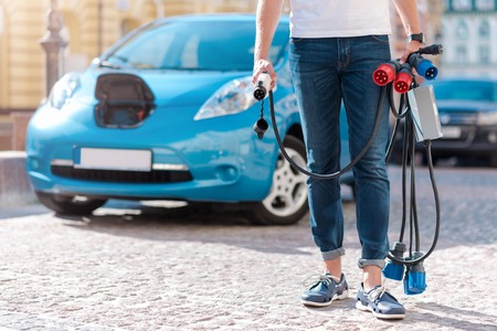electric automobile: Enjoy new possibility. Close up of a man standing in front of an electric automobile with a lot of power cables in his hands