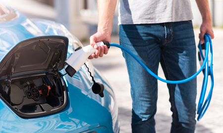 Lets turn it on. Close up of hands of a man plugging a power connector in an electric vehicle to fuel it