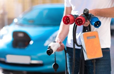 Así útil. Cierre de conectores de alimentación en manos de un hombre con un coche eléctrico en el fondo