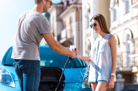 Try to do it. Confident pleasant man giving a power connector to a woman in front of their electric vehicle