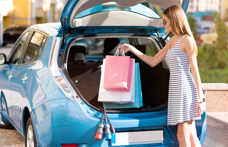 pastime: My favorite pastime. Lovely young woman with sunglasses putting bags of purchases in the open trunk of her eco car Stock Photo