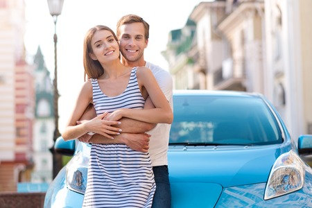 Sweet feelings. Charismatic young man keeping a delightful woman in his hands while standing in front of an electric vehicle