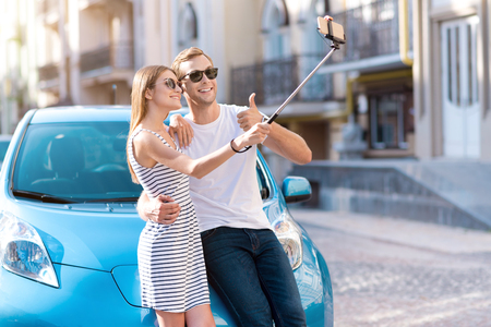 say cheese: Say cheese. Charming young couple relaxing and taking selfie with a monopod in front of their eco car