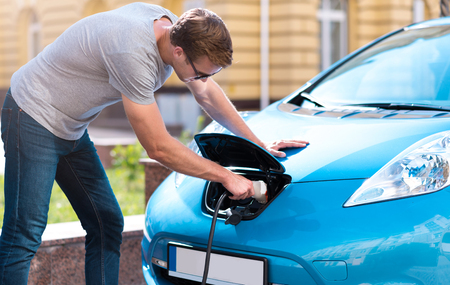 plugging: I have no problem with it. Handsome young man plugging his eco car for charging a battery in the city Stock Photo