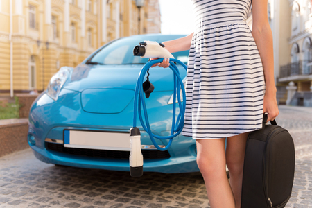 electric automobile: Easy even for me. Close up of a woman standing in front of an electric automobile with a lot of power cables in her hands