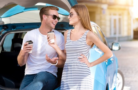 amiable: Pleasant time. Cute young woman and amiable handsome man sitting and talking on the trunk of their hybrid car and having coffee