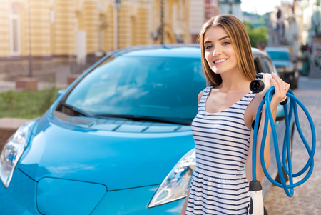 Totally in love with this car. Charming sincere woman holding a power cable to the electric vehicle while standing in front of one Stock Photo