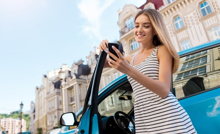 hybrid car: So interesting. Lovely smiling woman looking at her smartphone while standing near the open door of her hybrid car with the beautiful city on the background Stock Photo