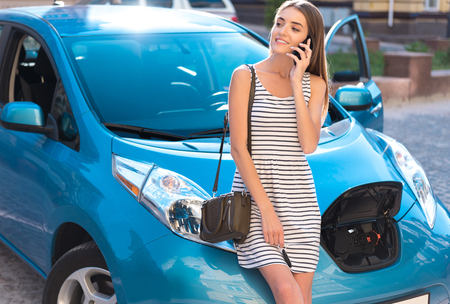Lets make a call. Calm young woman looking aside while calling with the smartphone and reclining on the eco car with the open fuel tank