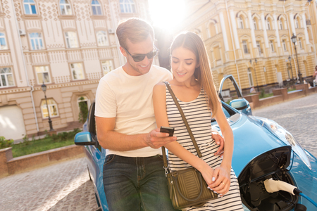 Darling, look here. Adorable young couple sitting on the hood of their electric car and looking at the smartphone with a sunset on the background