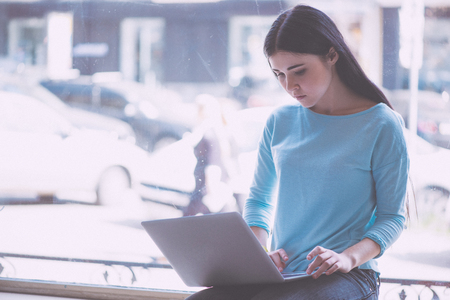 hardworking: Hardworking one. Busy and serious young woman sitting on a window sill and using laptop while being in a cafe