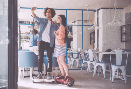 electronic balance: Time for selfie. Cheerful and content young people riding an electronic scooter smart balance wheel while being indoors in a cafe and making selfies Stock Photo