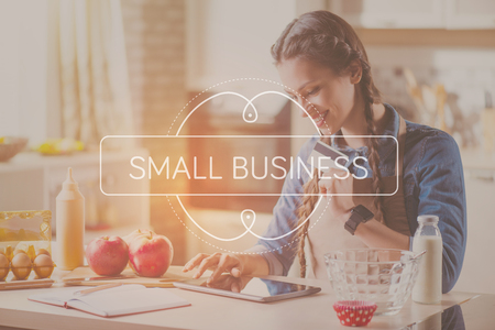 business help: Online payment. Inspirational typographic quote of small business with smiling young woman buying something online with help of tablet computer and credit card in a background