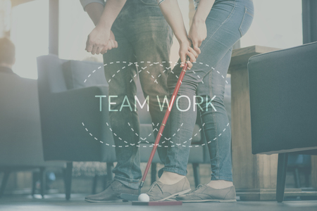 harmonize: Togetherness. Inspirational typographic quote about teamwork with cropped image of two friends playing golf indoors in a background Stock Photo