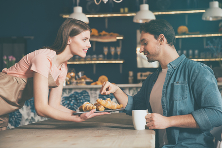 satisfied customer: Enjoy your meal. Delighted and positive female waitress giving croissant to her satisfied customer Stock Photo
