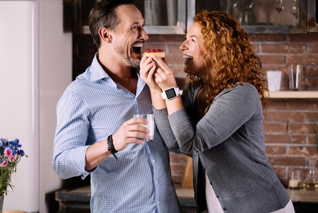 exciting: Open your mouth. Exciting woman feeding her husband with a delicious cake while standing in the kitchen and looking at him
