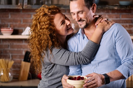 twining: Pleasant moment. Fantastic woman twining her hands around the neck of the man while looking at him and standing in the kitchen