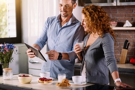 enquiring: Look here. Handsome man showing a photo on the tablet to his beautiful wife who looking at it with interest while having breakfast in the morning Stock Photo