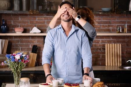 enquiring: Guess who. Exciting woman closing eyes of his cheerful man while standing in the kitchen at home