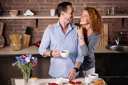 enquiring: Have a nice day. Delighted man holding a cup of coffee and looking at his wife who embracing him in the kitchen