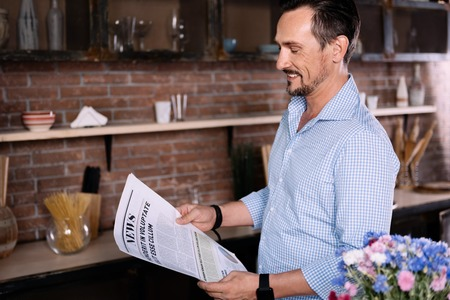 respectful: Pleasant article. Joyful bearded middle-aged man reading a newspaper while being in the kitchen in the morning